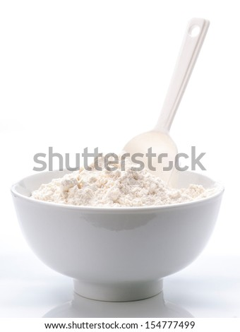porcelain white bowl with spoon full of flour - stock photo