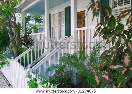 porch and picket fence along quiet side street in key west florida - stock photo