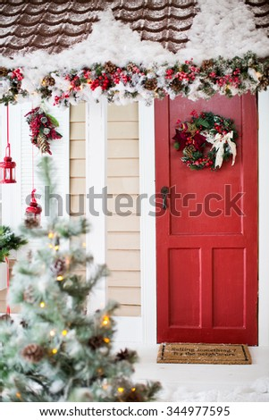 Porch with red door and christmas decorations - stock photo
