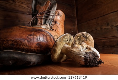 Porcini mushrooms on a wooden cutting board with a boot carved