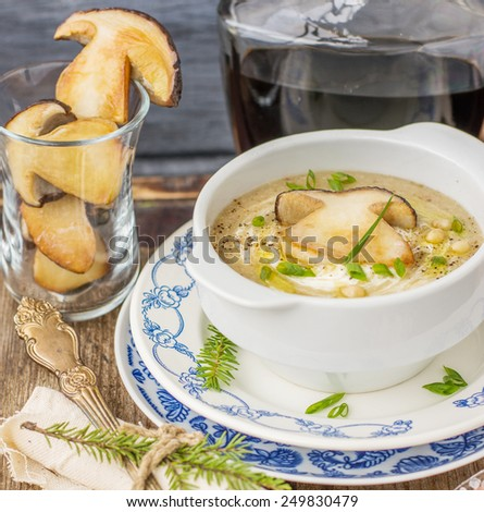 porcini soup puree with pine nuts in a white plate on a wicker tray on a wooden background with herbs. Selective focus