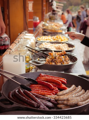 Pork, beef and paprika sausages,  hot dogs and  other appetizing, warming and usually unhealthy street fast food on an autumn Christmas market - stock photo