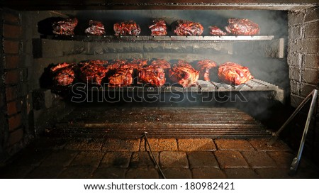 Pork being barbequed in a southern style pit over hickory wood. - stock photo