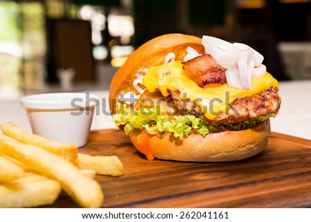 Pork burger with cheese, vegetable and served with fries - stock photo