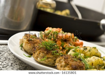Pork burgers with potatoes, carrot and green peas - stock photo