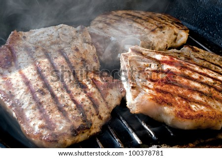 Pork chop grilled with delicious toasted traces and fragrant smoke - stock photo