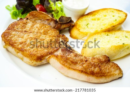 Pork chop served with  garlic bread and salad