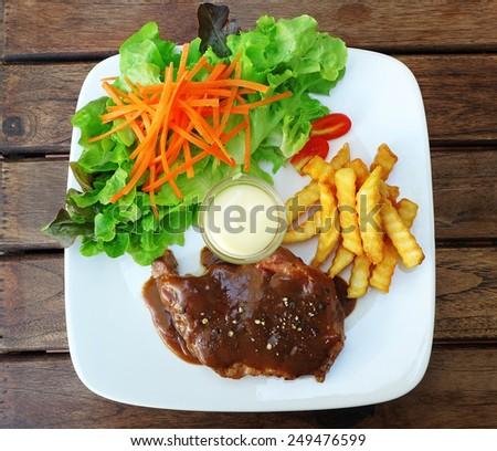 Pork chop steak with potato fried, vegetable in black pepper sauce - stock photo