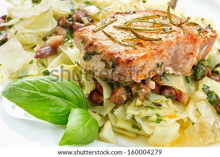 Pork chop with basil pesto, cabbage and bacon - stock photo