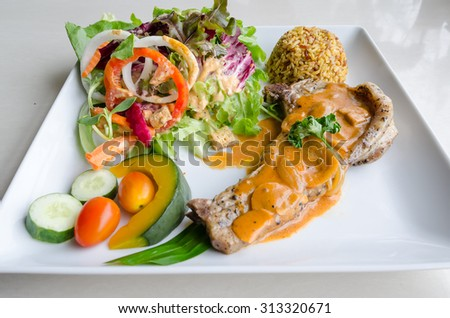 Pork Chop with mustard sauce, brown rice and salad - stock photo