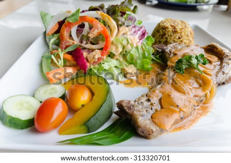 Pork Chop with mustard sauce, brown rice, salad on white ceramic dish - stock photo