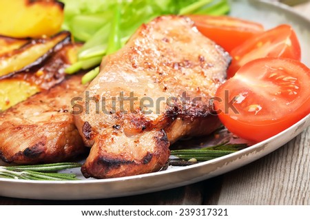 Pork chop with orange sauce and rosemary, close up view