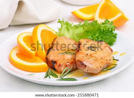 Pork chop with orange sauce on white plate - stock photo