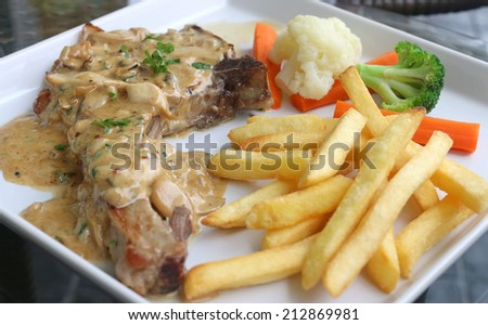 Pork chop with potato fried, vegetable and mushroom sauce - stock photo