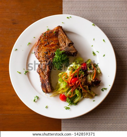 Pork chop with salad on table top view - stock photo