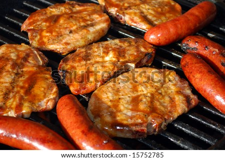 Pork chops and sausage barbecuing on the grill - stock photo