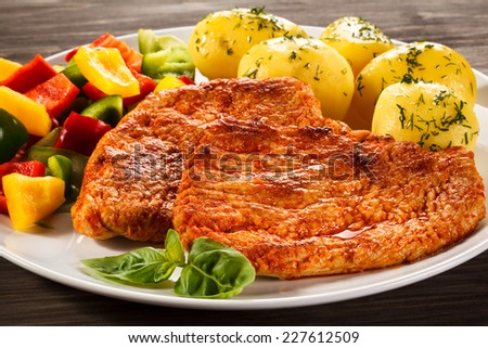 Pork chops, boiled potatoes and vegetables - stock photo