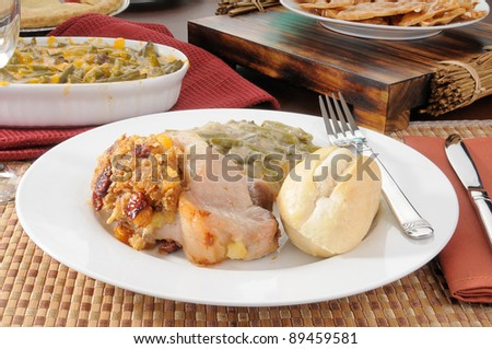 Pork chops stuffed with dried cherries and dressing and served with green bean casserole - stock photo