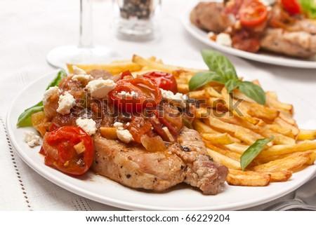 Pork Chops with Fresh Tomato, Onion, Garlic, and Feta - stock photo