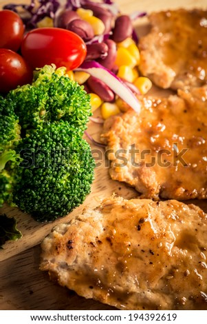 Pork cube steak topped with pepper sauce and creamy salad on wood plate