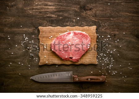 Pork cutlet. A piece of raw meat ready for preparation with spices on wooden table.