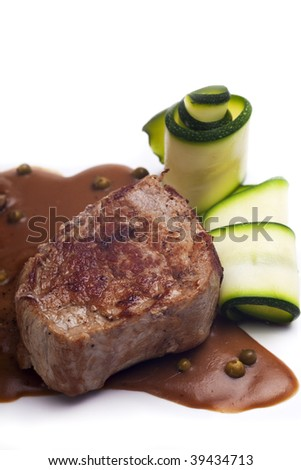 pork fillet and a brown pepper sauce on a white plate - stock photo