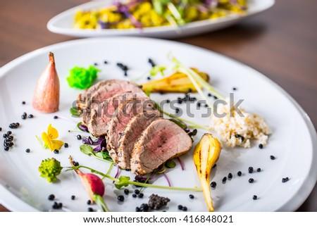 Pork Fillet. Pork meat. Pork fillet sirloin on plate with modern vegetable decoration in hotel restaurant. - stock photo