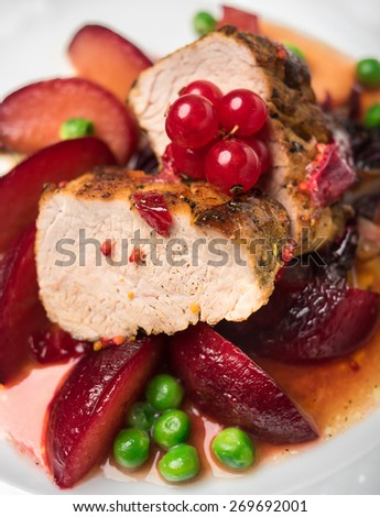 Pork fillet with apples, peas and red currant, selective focus - stock photo
