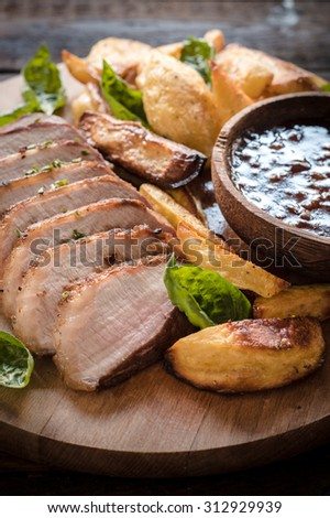 Pork fillets, baked potatoes and homemade bbq sauce on wooden background,selective focus