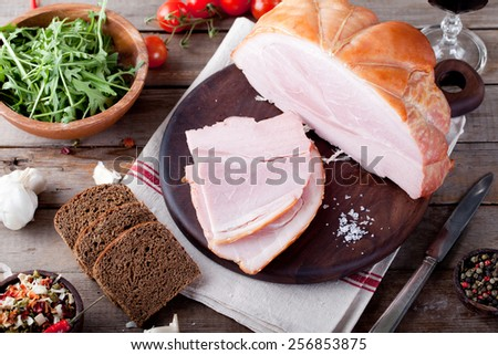 Pork ham on a wooden cutting board with fresh salad and vegetables.  - stock photo