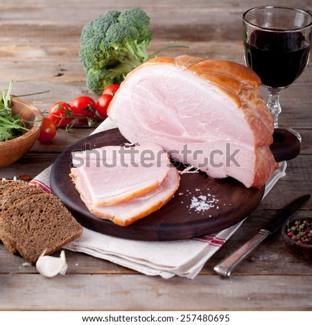 Pork ham on a wooden cutting board with fresh salad and vegetables.
