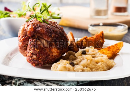 Pork knuckle with fried sauerkraut and salad