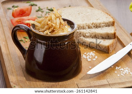 Pork lard with the fried onion in the pot and dark bread - stock photo