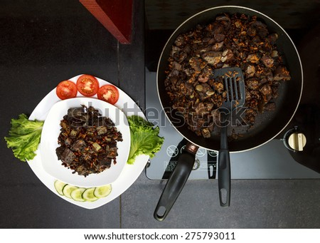 Pork liver stewed with onions and carrots and red beans in  frying pan served with vegetables on white plate view 1 - stock photo