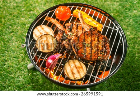 Pork loin and assorted fresh healthy vegetables grilling on a barbecue outdoors on green grass in a summer lifestyle concept - stock photo