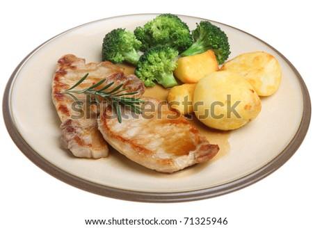 Pork loin steaks with roast potatoes, broccoli and gravy. - stock photo