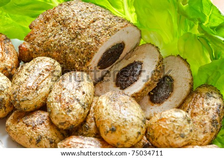 Pork loin with dried plums and baked potatoes - stock photo