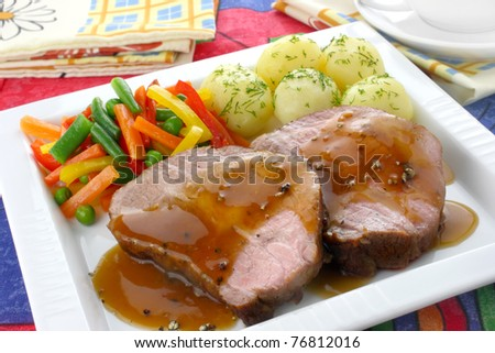 Pork meat with vegetables and sauce - stock photo