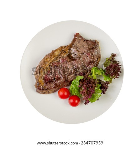 Pork neck steak with vegetables on plate isolated on white background
