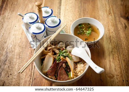 Pork noodle and fish ball with chopstick and spoon on wood background.thai food. - stock photo