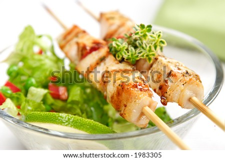 pork (or chicken) on a grill spit with salad and a slice of lime and lemon-thyme as garnish - stock photo