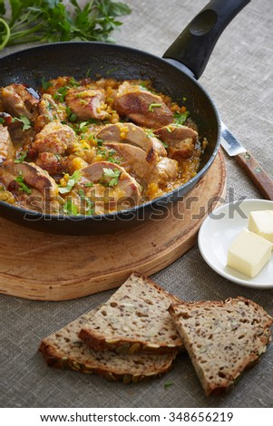 pork pieces in a frying pan on the cutting board