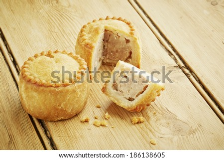 Pork pies sliced on wooden table top - stock photo