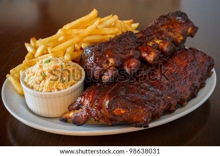 Pork ribs back with french fries and coleslaw salad on the side. Shallow depth of field. - stock photo