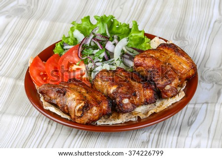 Pork ribs bbq with tomato, bread, salad leaves and onion