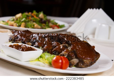 Pork Ribs with Sauce and Garnish on Plate on Restaurant Table - stock photo