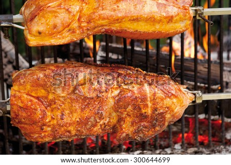 Pork roast with crackling roasting on charcoal grill