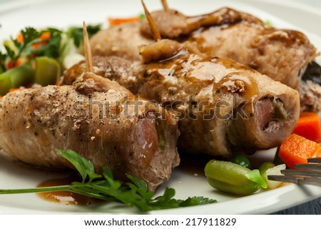 Pork rolls and vegetables on plate - stock photo
