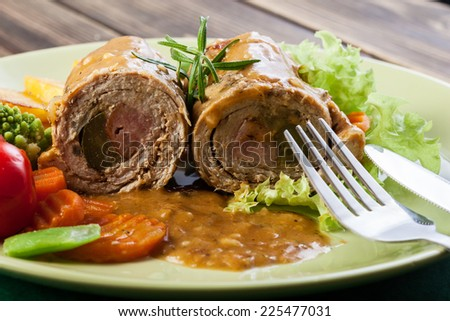 Pork rolls with prepared potatoes and vegetables on plate - stock photo
