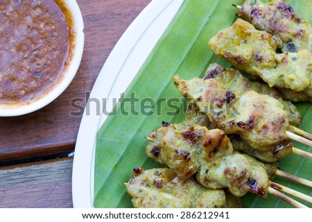 Pork Satay with delicious peanut sauce, one of famous local dishes. - stock photo